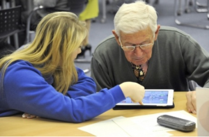 a pupil helping an old man use his iPad