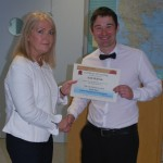 Photograph of Steering Group Representative awarding a certficate