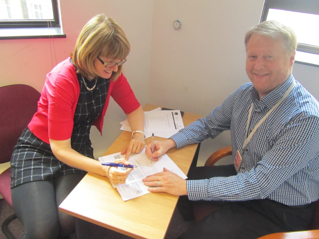 Man and woman signing-up for an apprenticeship