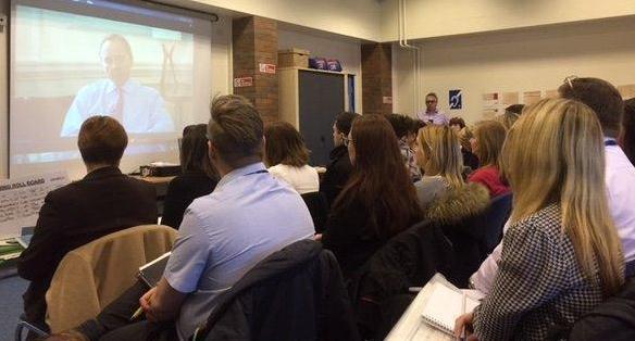 Delegates watching a video presentation by John Manzoni