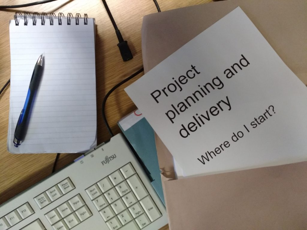 Keyboard, notepad and folder called Project planning and delivery