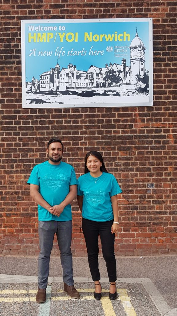 Gail and Koysar standing under a picture welcoming to HMP YOI Norwich a new life starts here
