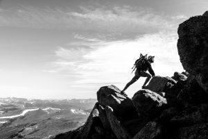 man climbing up a mountain