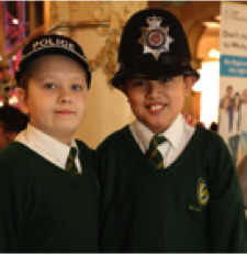 Two young students wearing Police Officer's hats