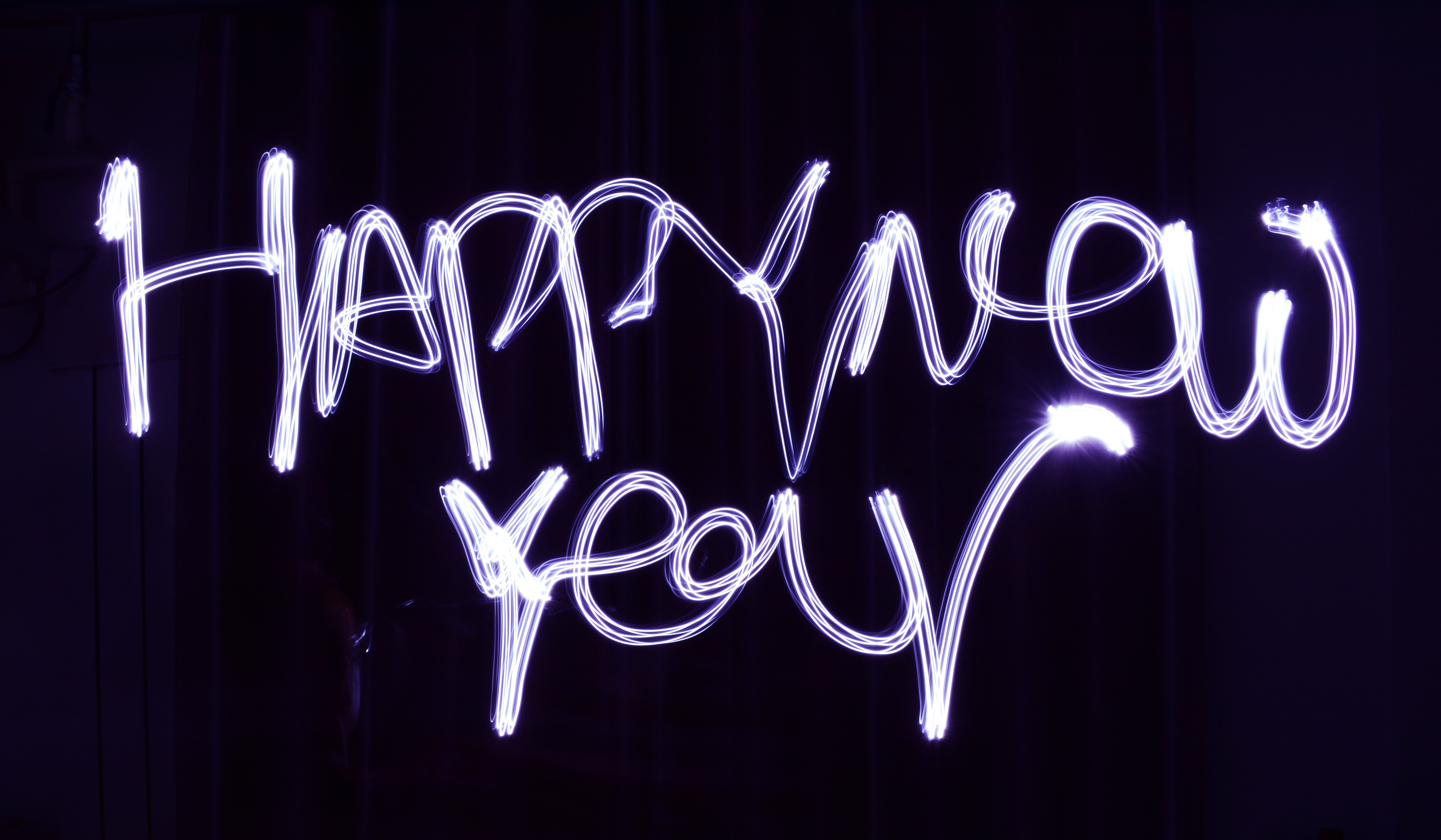 "The words ""Happy New year"" written with a purple sparkler on a black background"