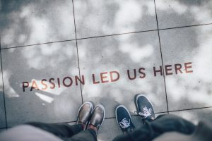"Two pairs of feet on a pavement with the caption ""Passion led us here "" written on the ground"