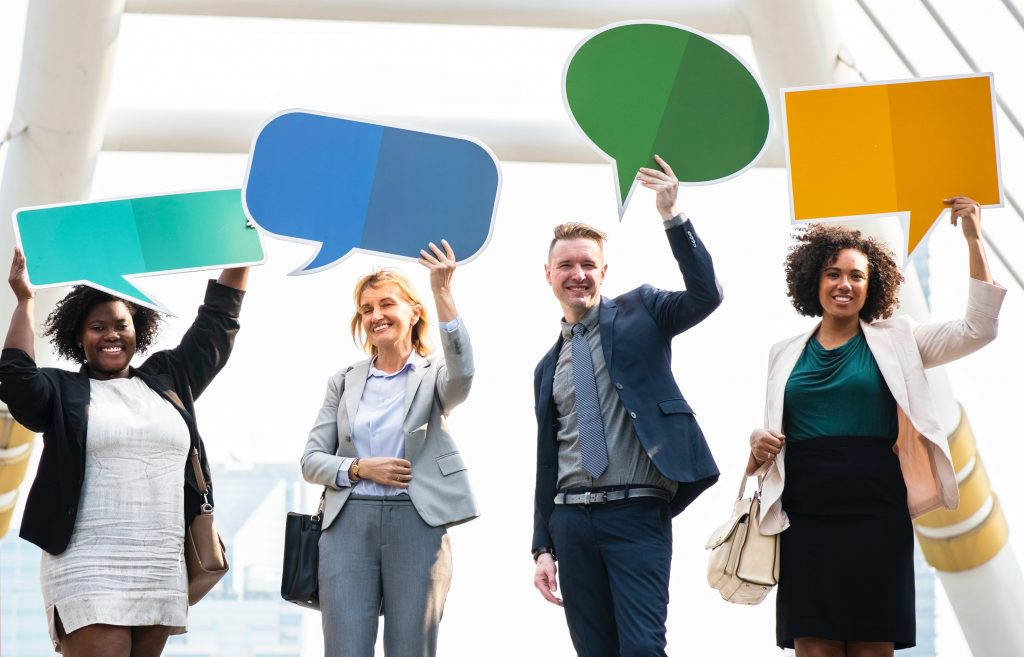 Four people holding up cardboard speech bubbles