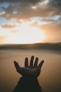 Hand reaching into sunset