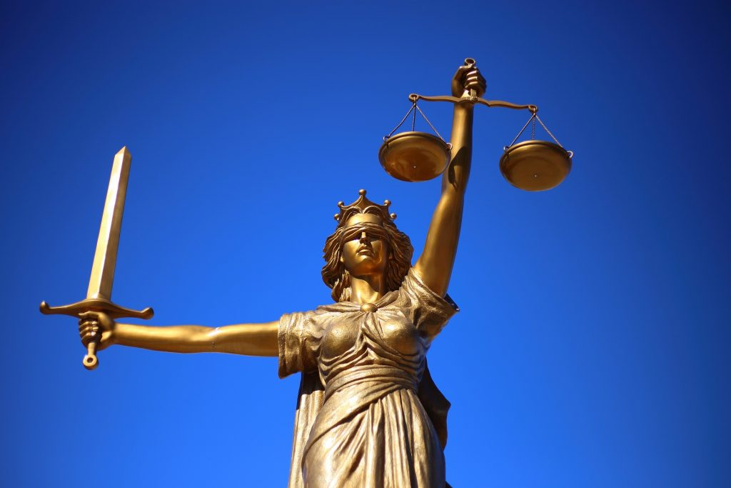 bronze statue of justice against a blue sky