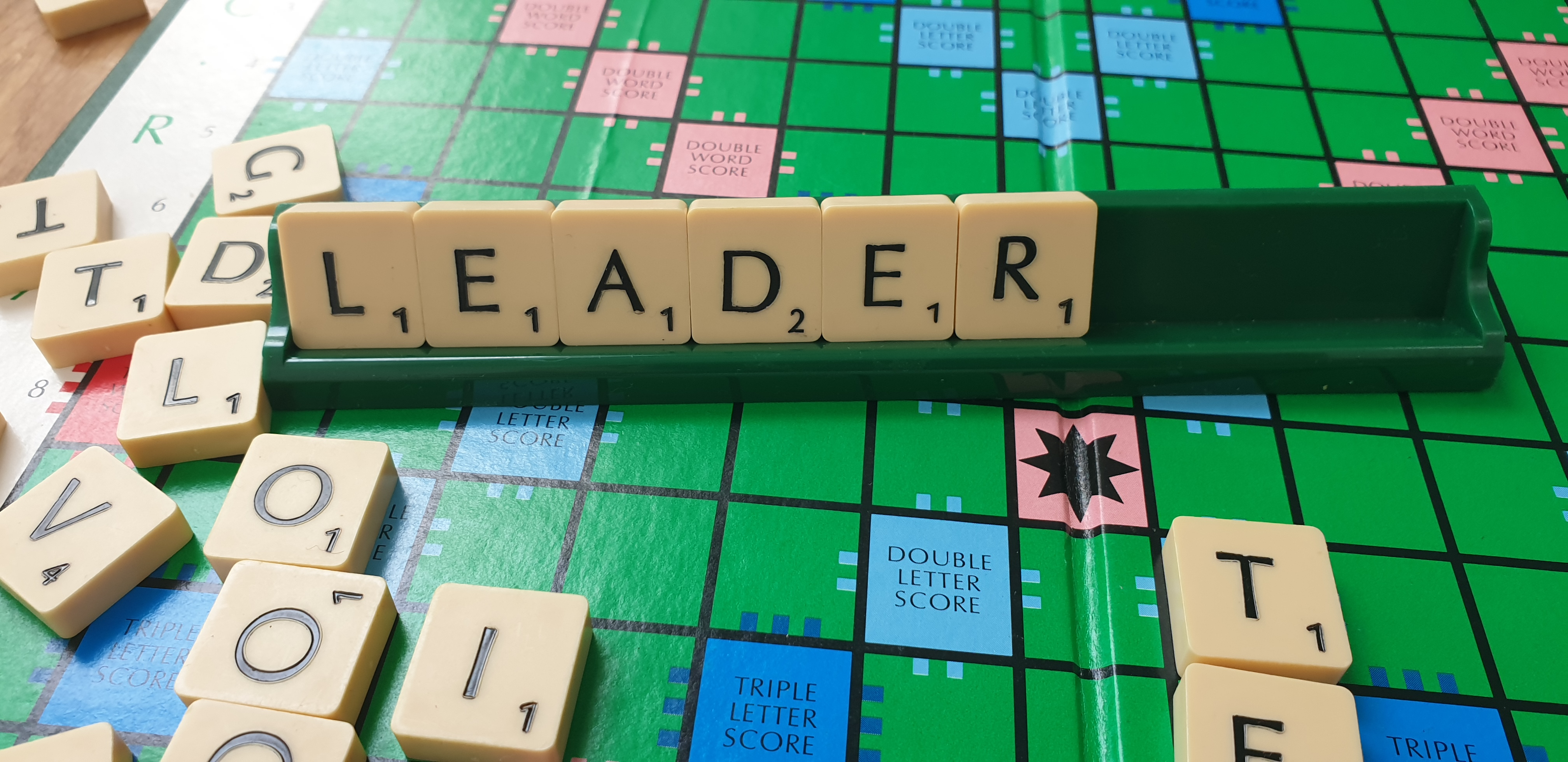 Scrabble board with the word leader splet out using scrabble tiles