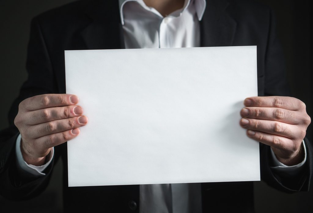 man holding up blank sheet of paper