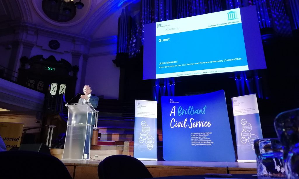 "John Manzoni speaking at a podium on stage at the showcase event underneath a beautiful chandelier in front of a large banner which reads ""A Brilliant Civil Service"""