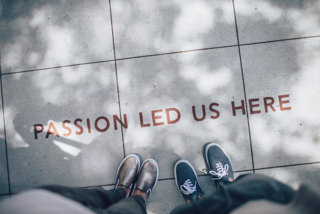 people looking down at a sign written on the pavement saying passion led us here