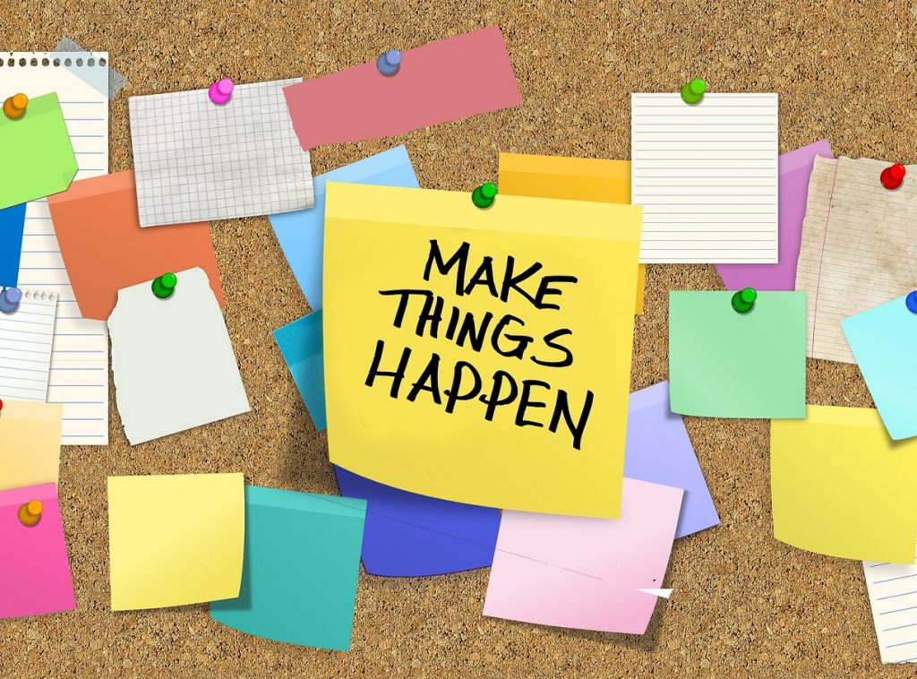 Bulletin board with post its and middle one saying make things happen