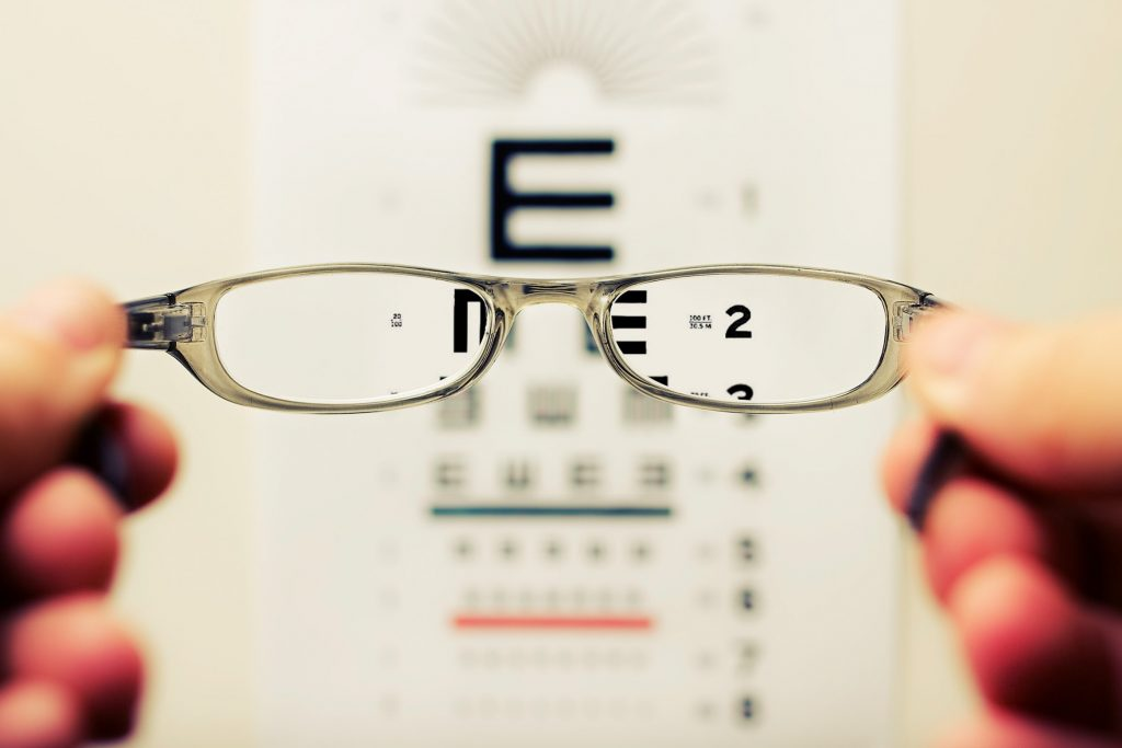 A pair of spectacles being held in front of an eyesight test board.