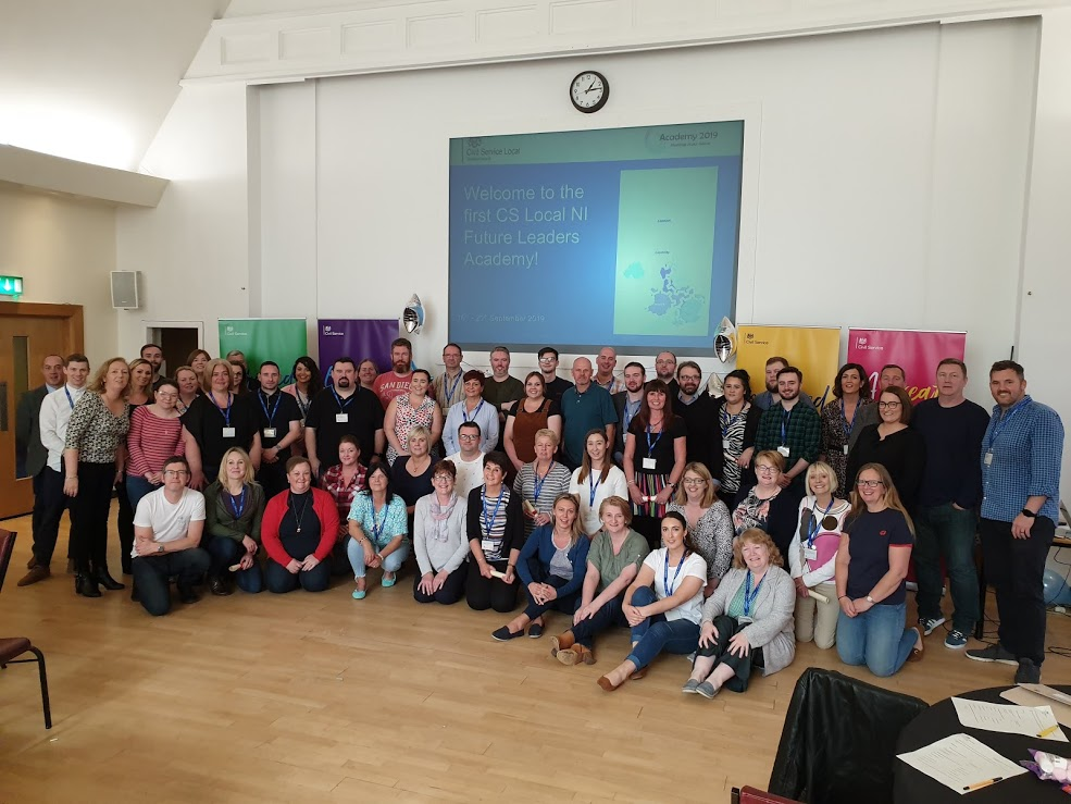 """all the delegates, facilitators and project team standing in staggered rows in front of a screen which says """"Welcome to the first CS Local NI Future Leaders Academy""""."""