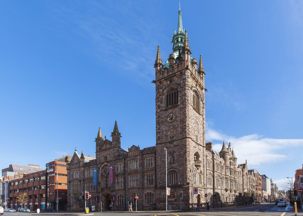 a beautiful gothic building with a large clock tower reaching up into the blue sky.