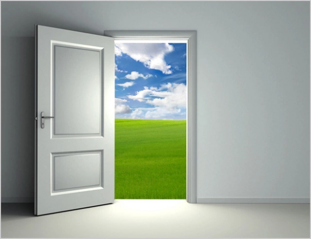 Open door showing grass and clouds the other side