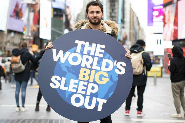 a man holding a large dark blue circular sign with a picture of the world on it and the words the worlds big sleep out in large white text