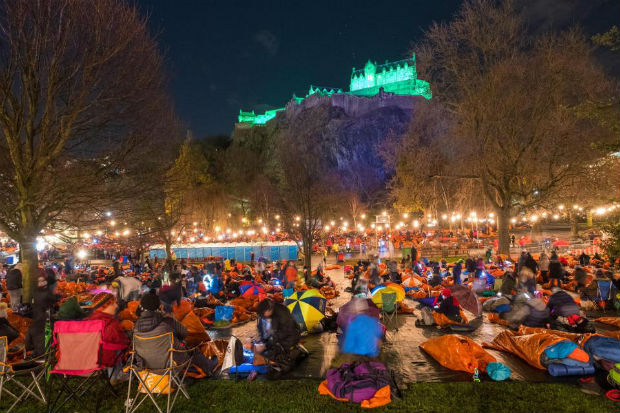 groups of people in sleeping bags in Princes street gardens Edinburgh with the castle overlooking them