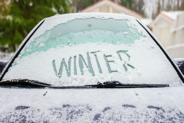 A car covered in frost with the word winter etched on the windscreen in capital letters