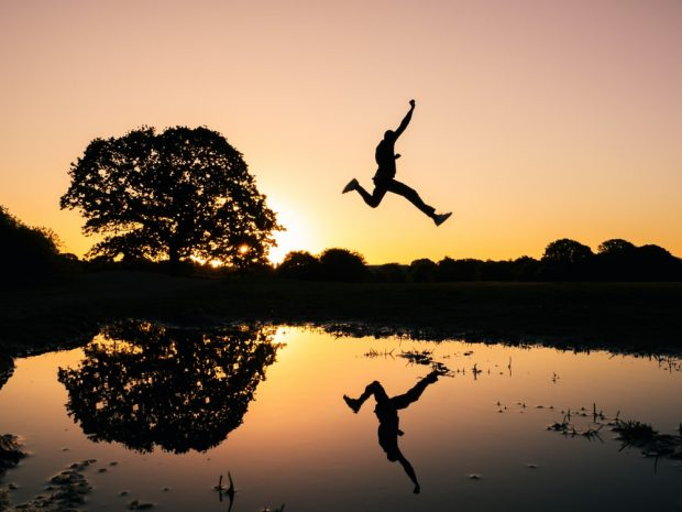 Man jumping over body of water during sunset