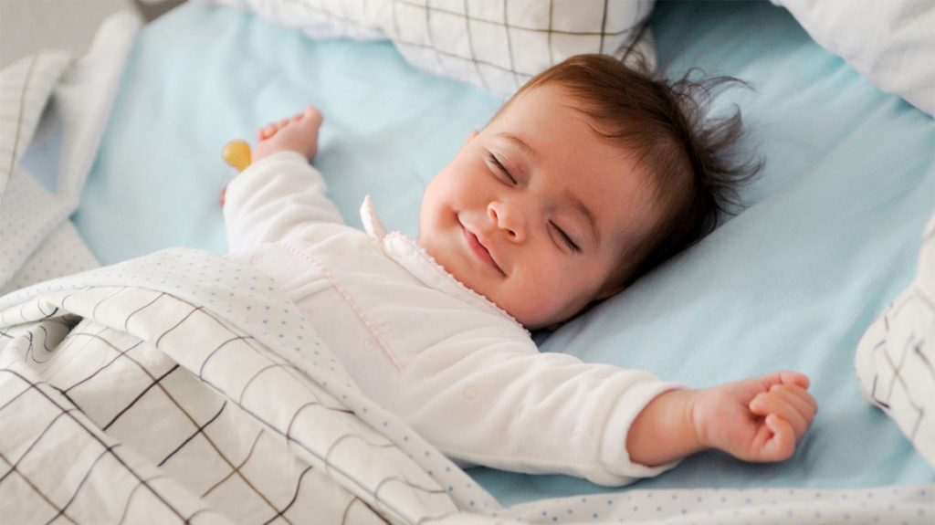 Baby sleeping on its back with arms out to its side and smiling with a checked blanket mid way up its body