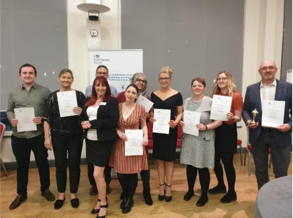 Members of the shadow network standing together holding certificates