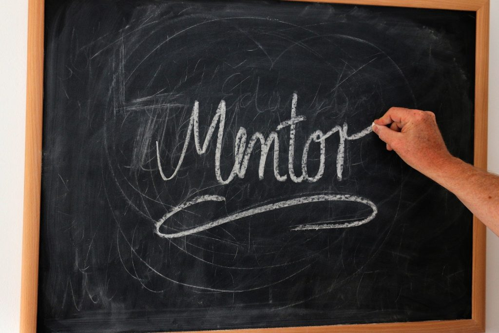 Chalk board with hand writing the word 'mentor'