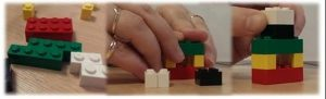 A pair of hands building with lego blocks