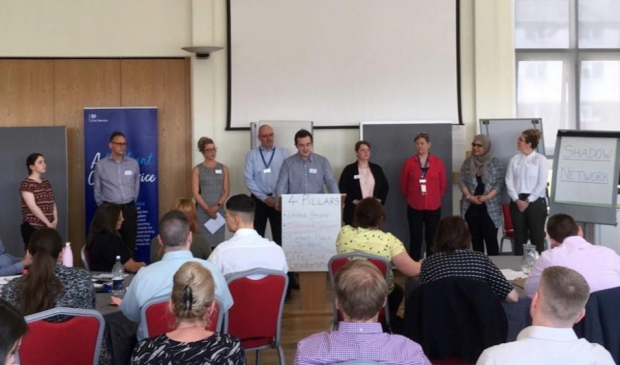 Academy delegates standing in front of other delegates presenting their plans