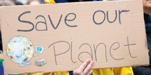 A brown Board with writing on Save our Planet with a little globe sign on right hand side corner