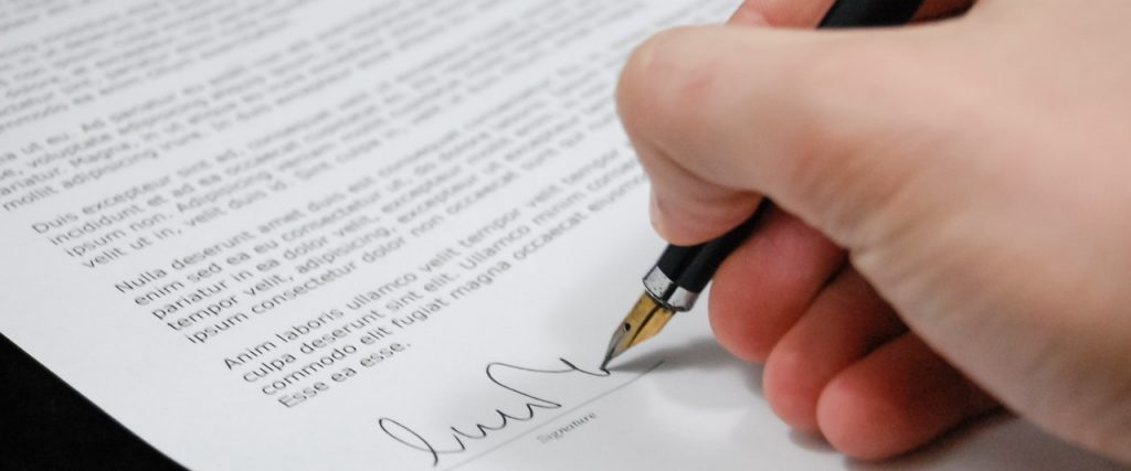A hand holding a fountain pen signing an official looking document