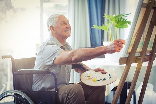 A smiling gentlemen in a wheelchair painting on a canvas with a paint board in his left hand