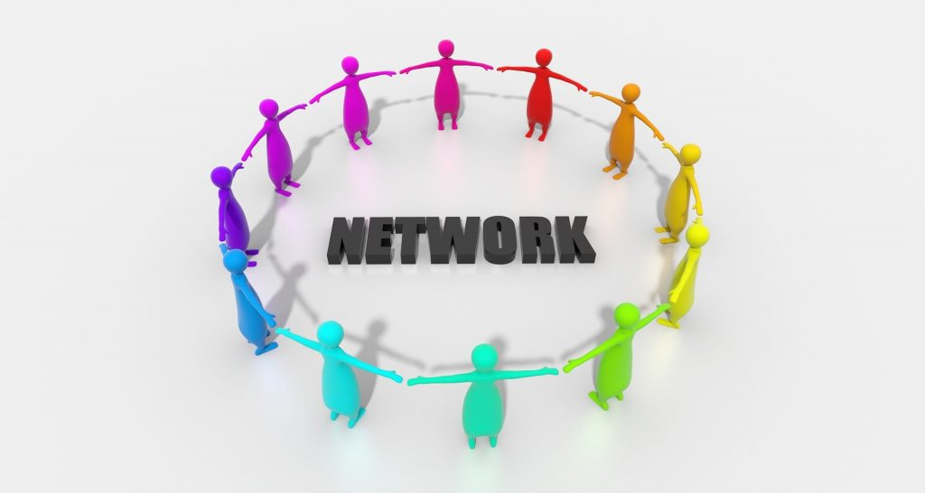 Multicoloured people shaped pegs forming circle around the word Network