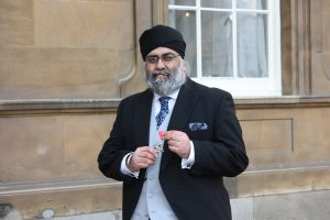 MR Amrik Singh Bahbra holding a MBE honour medal