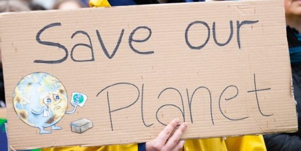 A cardboard sign saying 'save our planet'