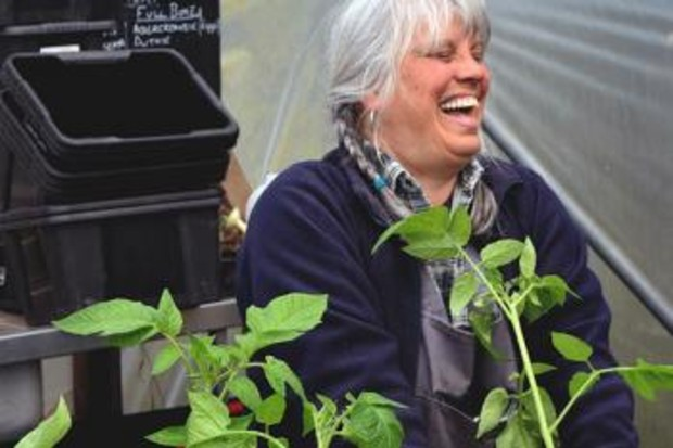 a woman laughing while potting plants