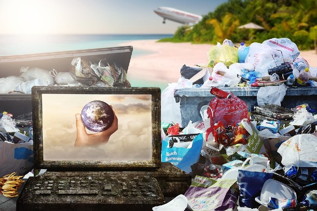 computer screen with world in hand and rubbish left on beach at righthand side and aircraft in background