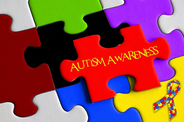 multi colour jigsaw pieces with autism awareness written in centre