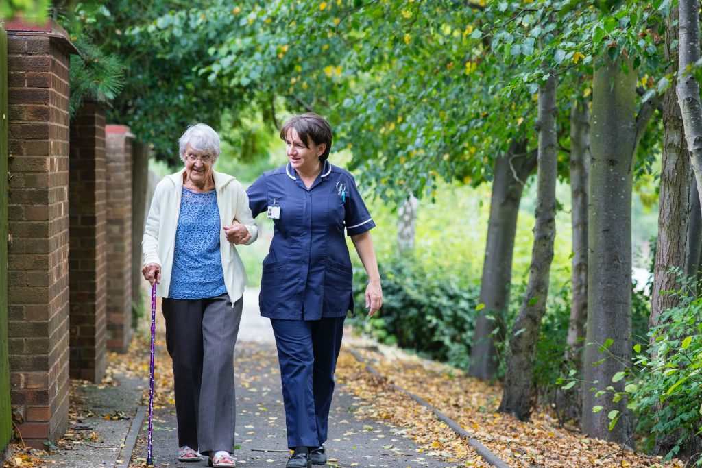 Nurse holding the arm of an person with Dementia along a path