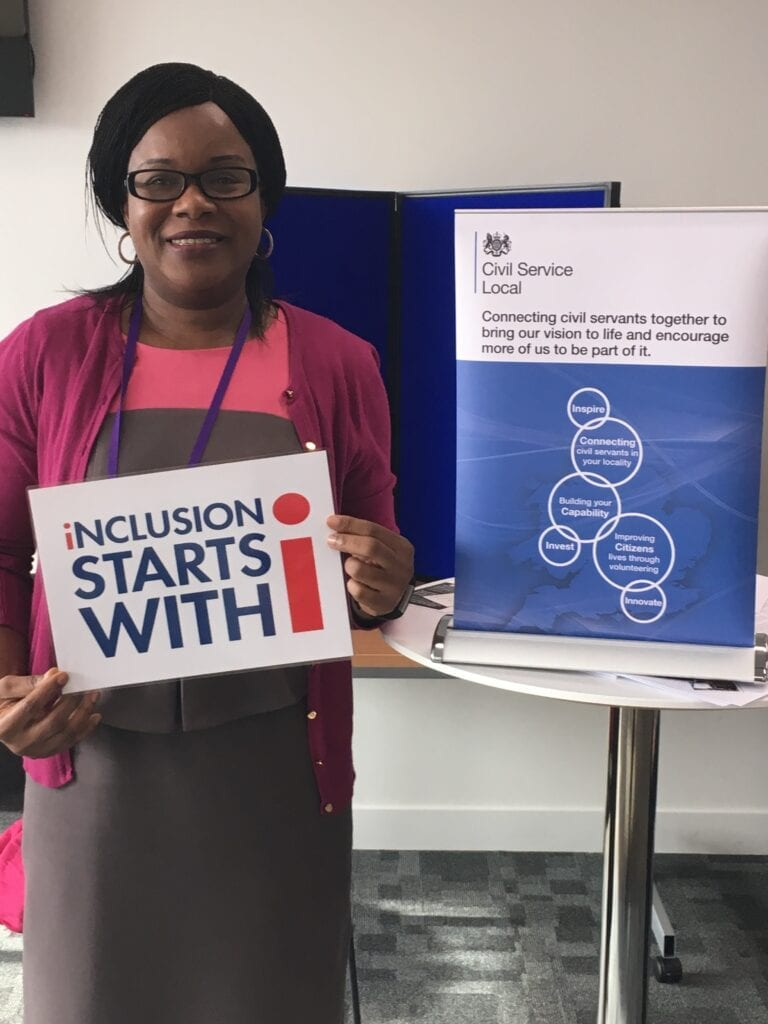 """A picture of Bernadette Thompson OBE holding a sign saying """"Inclusion starts with I"""""""