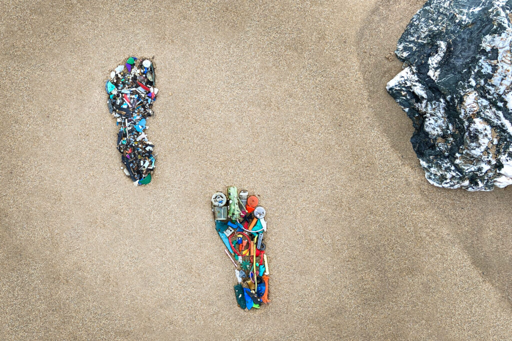 beach with plastic waste in the shape of feet
