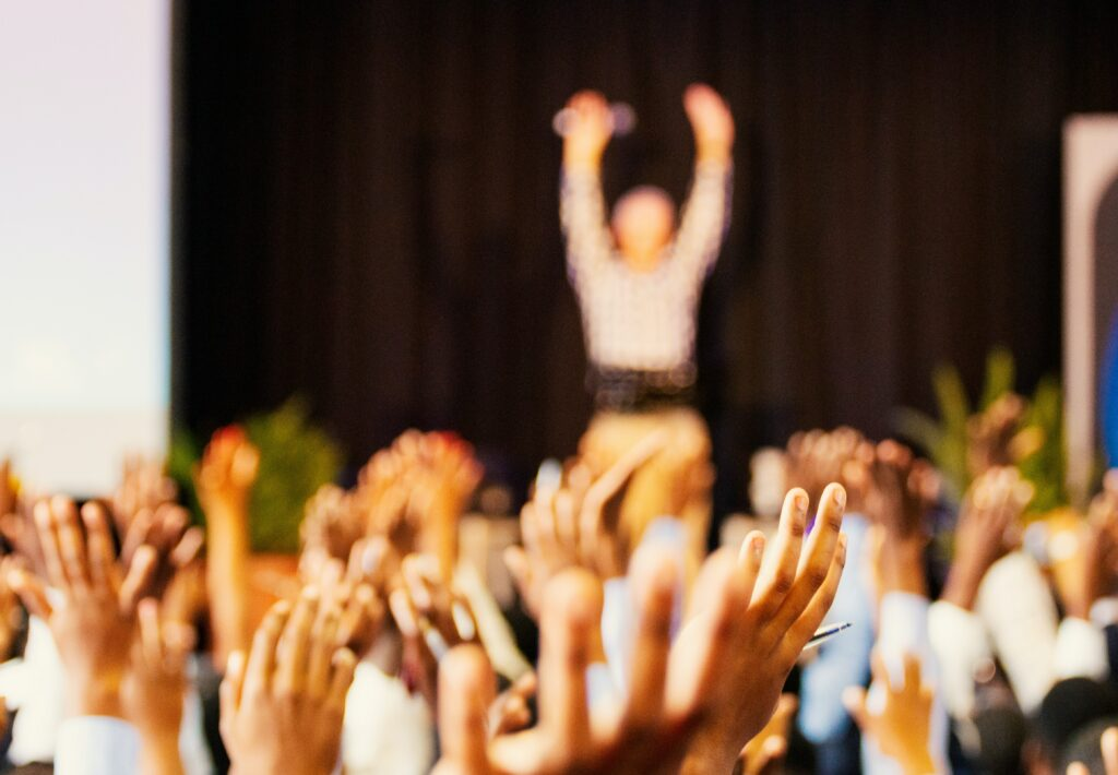 a room of people with raised hands